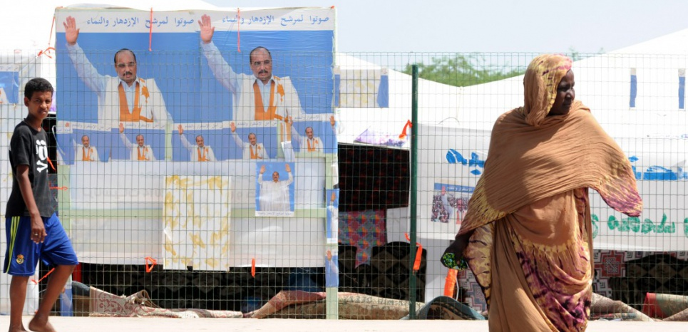 A woman crosses a street in front of campaign posters of Mauritania's outgoing president and candidate to his succession Mohamed Ould Abdel Aziz in Nouakchott on June 19, 2014, on the last day of campaining  ahead of the June 21 presidential poll. The Islamic Republic of Mauritania is led by Mohamed Ould Abdel Aziz, an ex-general who led a 2008 coup and won election a year later, who is tipped to win the upcoming elections, amid a boycott by leading opposition groups.    AFP Photo Seyllou