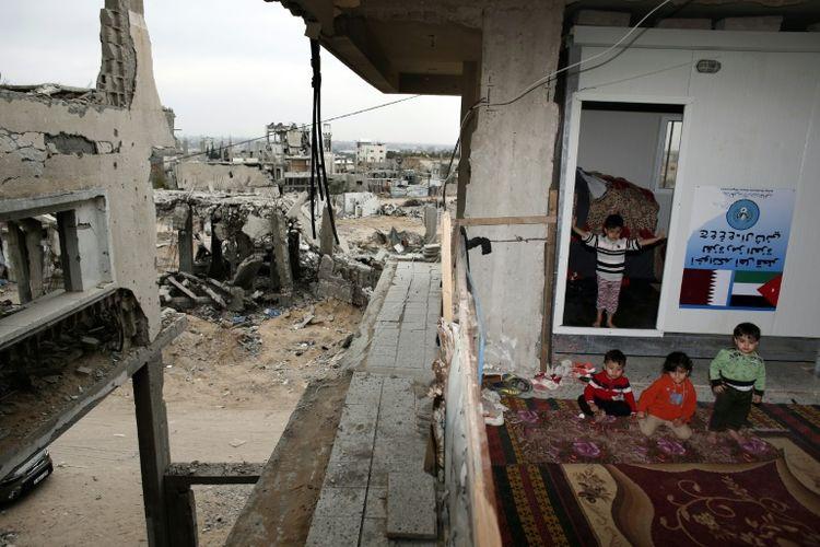 790096-des-enfants-palestiniens-devant-leur-maison-detruite-a-shujaiya-le-11-mai-2015