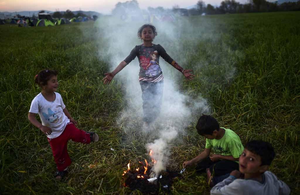 Autour d'un feu dans le camp de réfugiés d'Idomeni (AFP / Bulent Kilic)