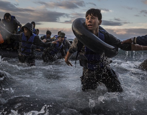 After battling rough seas and high winds from Turkey, refugees arrive by rubber raft on a jagged shoreline of Lesbos. Fearing capsize or puncture, some panicked and jumped into the cold water in desperation to reach land (The New York Times/Tyler Hicks - October 1, 2015). 1