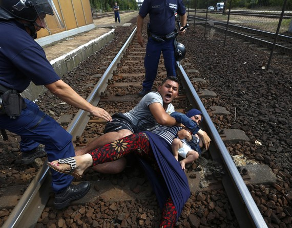 A police officer tries to stop someone from boarding a train through a window at Gevgelija train station in Macedonia, close to the border with Greece (Thomson Reuters/Stoyan Nenov - August 15, 2015).