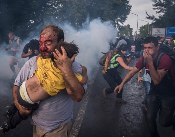 A man tries to shield his child from police beatings and tear gas at the border crossing in Horgos, Serbia (The New York Times/Sergey Ponomarev - September 16, 2015).