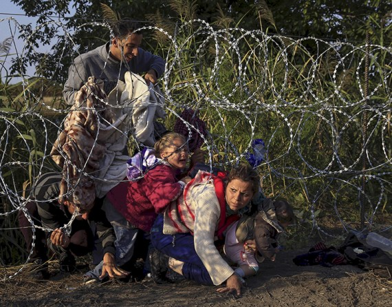 Syrian migrants cross under a fence as they enter Hungary at the border with Serbia, near Roszke (Thomson Reuters/Bernadett Szabo - August 27, 2015).