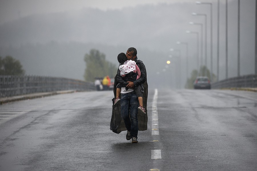 A Syrian man kisses his daughter as he walks through a rainstorm towards Greece's border with Macedonia, near Idomeni (Thomson Reuters/Yannis Behrakis - September 10, 2015).