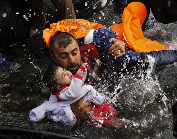 A Syrian refugee holds onto his children as he struggles to walk off a dinghy after crossing a part of the Aegean Sea from Turkey to Lesbos (Thomson Reuters/Yannis Behrakis - September 24, 2015).