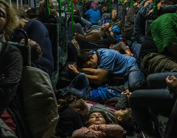 Ahmad Majid, in blue T-shirt at centre, sleeps on a bus floor with his children, his brother Farid Majid, in green sweater at right, and other members of their family and dozens of other refugees, after leaving Budapest on the way to Vienna. (The New York Times/Mauricio Lima - September 5, 2015).