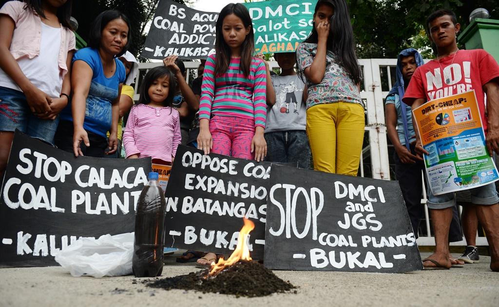 Des résidents de Calaca regardent brûler un tas de terre ramassé à côté de la centrale à charbon dans leur ville, lors d'une manifestation devant le bureau du ministère de l'Environnement à Manille aux Philippines le 17 mars 2016. (Crédits : TED ALJIBE / AFP)