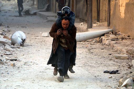 Dans les rues d'Alep, un homme porte sur son dos un blessé, après une frappe aérienne.• Crédits : Mamun Ebu Omer / ANADOLU AGENCY