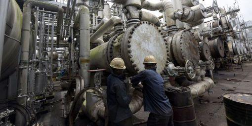 Ouvriers nigérians intervenant dans une raffinerie de pétrole à Port Harcourt (sud du Nigeria), le 16 septembre 2015. © AFP - PIUS UTOMI EKPEI