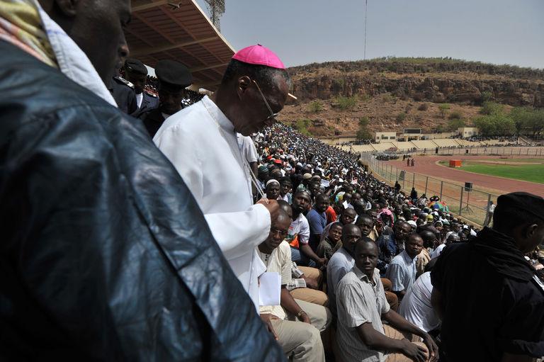 L'archevêque de Bamako Jean Zerbo arrive au Stade de l'amitié, en 2012, pour une prière pour la paix alors que les combats font rage au nord du pays. Crédits : ISSOUF SANOGO / AFP