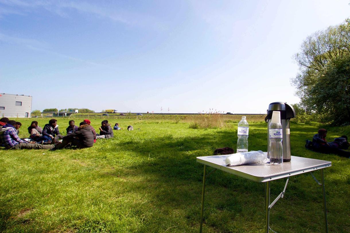 Une dizaine de jeunes migrants terminent leur petit-déjeuner près de la rocade portuaire de Calais (Photo de Pierre-Louis Caron/VICE News)