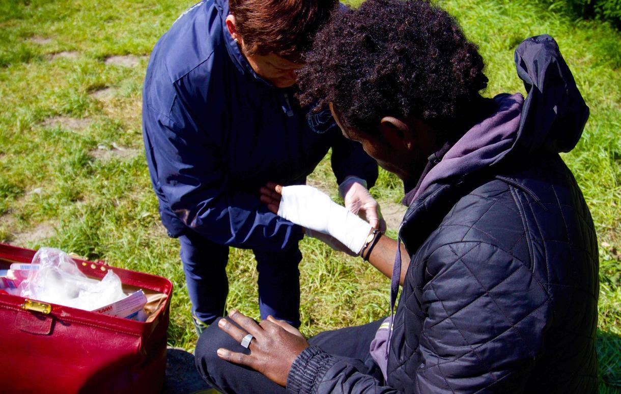 Yolaine, bénévole de l'association Salam, termine le pansement d'un jeune migrant blessé au pouce (Photo de Pierre-Louis Caron/VICE News)