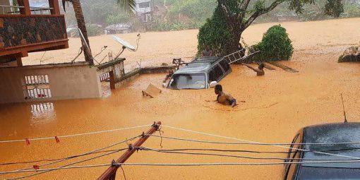 Un homme dans les rues inondées de Regent, près de la capitale de la Sierra Leone, Freetown le 14 août 2017  © STR / SOCIETY 4 CLIMATE CHANGE COMMUNICATION SIERRA LEONE / AFP