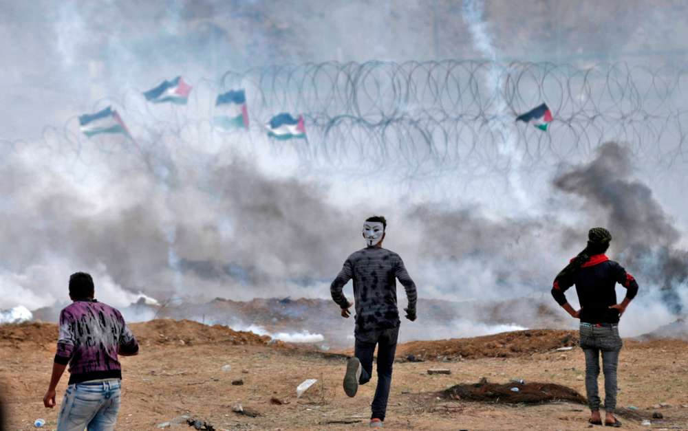TOPSHOT - Palestinian protesters demonstrate near the fence on the Israel-Gaza border, east of Gaza City in the central Gaza Strip, during the fifth straight Friday of mass demonstrations and clashes along the border with Israel on April 27, 2018. / AFP / MAHMUD HAMS