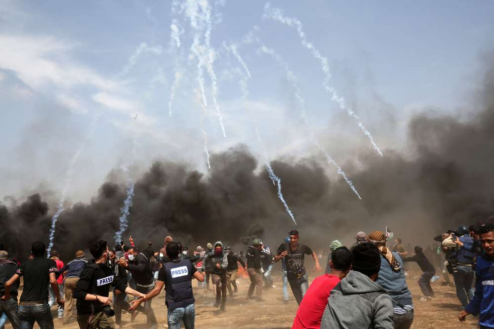 TOPSHOT - Palestinian demonstrators run for cover from tear gas fired by Israeli security forces near the southern Gaza Strip town of Khan Yunis during the fifth straight Friday of mass demonstrations and clashes along the Gaza-Israel border on April 27, 2018. / AFP / SAID KHATIB