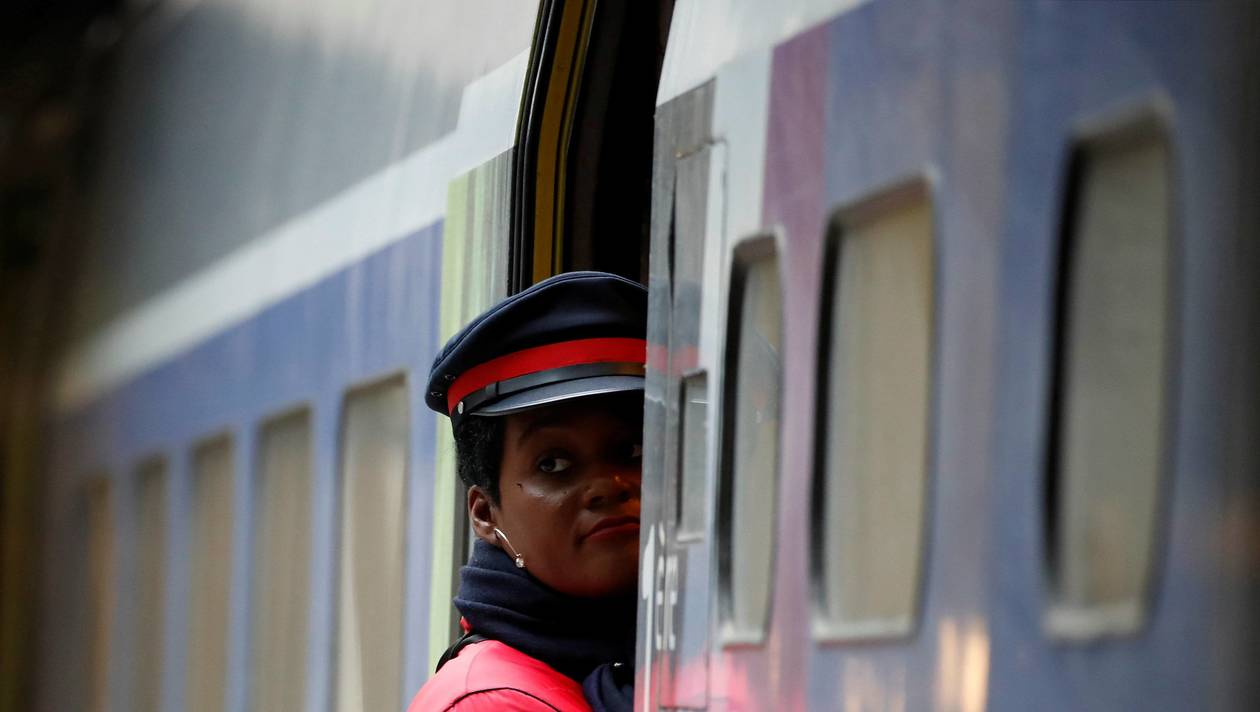 An agent waits for passengers to board a TGV high-speed train at Montparnasse railway station in Paris